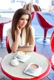 Ung kvinna som sitter i cafen med en kopp av tea Royaltyfria Foton