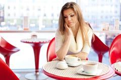 Ung kvinna som sitter i cafen med en kopp av tea Royaltyfria Bilder