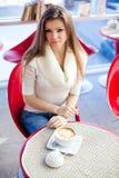 Ung kvinna som sitter i cafen med en kopp av tea Fotografering för Bildbyråer