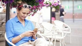 Ung kvinna som sitter i gatakafét på terrassen och använder hennes smartphone lager videofilmer