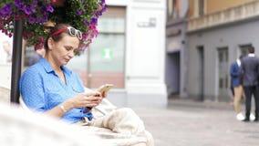 Ung kvinna som sitter i gatakafét på terrassen och använder hennes smartphone stock video