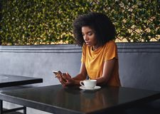 Ung kvinna som sitter i kafé genom att använda mobiltelefonen royaltyfri foto