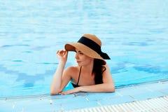 Ung kvinna som sitter nära pölen Sexig flicka med sund brunbränd hud Kvinnlig med solhatten som kopplar av i simbassäng royaltyfria foton