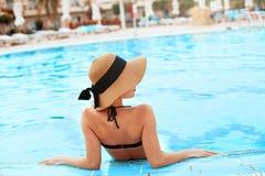 Ung kvinna som sitter nära pölen Sexig flicka med sund brunbränd hud Kvinnlig med solhatten som kopplar av i simbassäng royaltyfria bilder