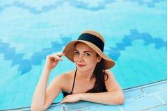 Ung kvinna som sitter n?ra p?len Sexig flicka med sund brunbr?nd hud Kvinnlig med solhatten som kopplar av i simbass?ng royaltyfri fotografi