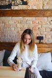 Ung kvinna som sitter nära tabellen med koppen kaffe och poserar för foto royaltyfri fotografi