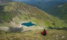 Ung kvinna som sitter och beundrar en härlig sjö i bergen royaltyfri fotografi