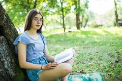 Ung kvinna som sitter och läser hennes favorit- bok på gröna gras för nolla under träd i en trevlig solig sommar royaltyfri bild