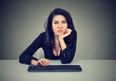 Ung kvinna som sitter på arbetsplatsen och förhalar vara lat och förstrött arkivfoto