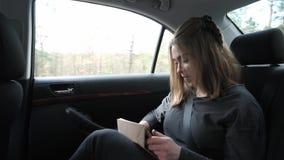 Ung kvinna som sitter på baksätet av en bil som ler stock video