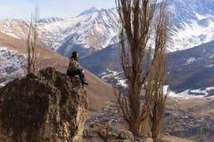 Ung kvinna som sitter på en hög sten och ser de snöig bergen royaltyfri foto