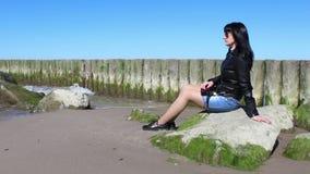 Ung kvinna som sitter på en sten vid havet lager videofilmer