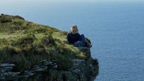 Ung kvinna som sitter på kanten av en klippa på den irländska västkusten arkivfilmer