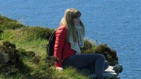 Ung kvinna som sitter på kanten av en klippa på den irländska västkusten stock video