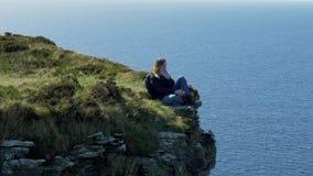 Ung kvinna som sitter på kanten av en klippa på den irländska västkusten lager videofilmer