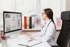 Ung kvinna som sitter på skrivbordet som arbetar på den moderna datoren med medicinska dokument i ljust kontor i sjukhus kvinnlig arkivfoto