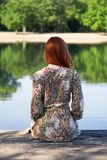 Ung kvinna som sitter på träpir som ser sjön royaltyfri fotografi