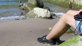 Ung kvinna som sitter p? en sten vid havet lager videofilmer