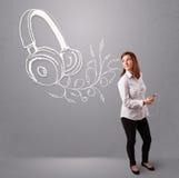 Ung kvinna som sjunger och lyssnar till musik med abstrakt headpho Royaltyfri Bild