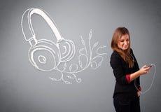 Ung kvinna som sjunger och lyssnar till musik med abstrakt headpho Arkivfoton