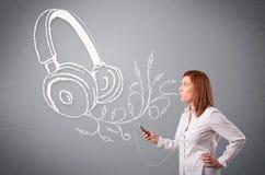 Ung kvinna som sjunger och lyssnar till musik med abstrakt headpho Arkivbild
