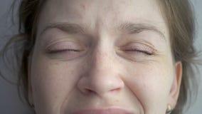 Ung kvinna som skelar och blinkaögon arkivfilmer