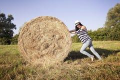 Ung kvinna som skjuter ett hö Arkivfoton