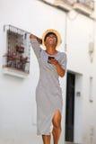 Ung kvinna som skrattar med mobiltelefonen Arkivfoton