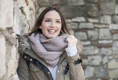 Ung kvinna som skrattar nära stenväggen Arkivfoto