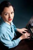 Ung kvinna som skrivar med den gammala skrivmaskinen Arkivfoto