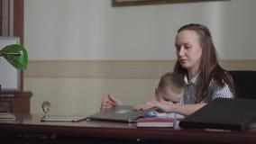 Ung kvinna som skriver p? hennes b?rbar dator som hemma sitter i bekv?m stol med ett barn Damen stoppar att arbeta och s?tter arkivfilmer