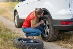 Ung kvinna som skruva av muttrar för bilhjul för att ändra det plana däcket Royaltyfria Foton
