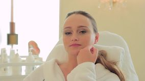 Ung kvinna som slår hennes framsida i en kosmetologs kontor lager videofilmer