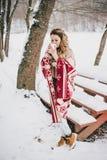 Ung kvinna som slås in i filten som dricker varmt te i snöig skog Royaltyfri Bild