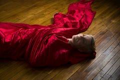 Ung kvinna som slås in i rött tyg som ligger på studiogolv Arkivfoto