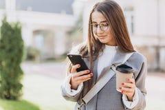 Ung kvinna som smsar eller använder smartphonen arkivbild