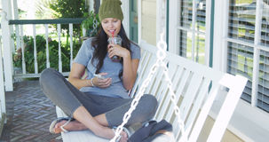 Ung kvinna som smsar och sitter på farstubron Arkivbild