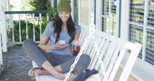 Ung kvinna som smsar och sitter på farstubron Arkivbilder