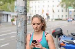 Ung kvinna som smsar på hennes mobiltelefon Arkivfoto