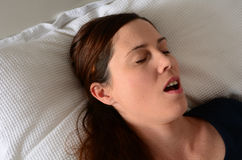 Ung kvinna som snarkar i säng Arkivfoto