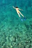 Ung kvinna som snorklar i tropiskt vatten på semester Royaltyfri Fotografi