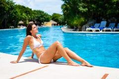 Ung kvinna som solbadar och kopplar av på semesterortsimbassängen Arkivbild