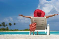 Ung kvinna som solbadar på dagdrivare på den tropiska stranden Royaltyfri Bild