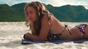 Ung kvinna som solbadar på sommarstranden på grön bergbakgrund Härlig kvinna i bikinisol som garvar på sandigt stock video