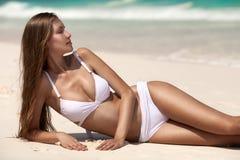Ung kvinna som solbadar på den tropiska stranden Fotografering för Bildbyråer