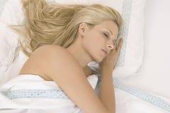 Ung kvinna som sovar i säng. Royaltyfri Foto