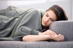 Ung kvinna som sovar på sofaen Royaltyfri Bild
