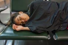 Ung kvinna som sover i flygplatsen royaltyfri foto