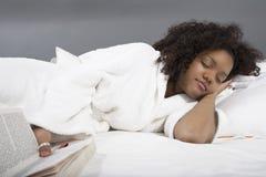 Ung kvinna som sover i säng royaltyfria foton