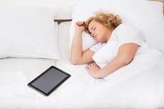 Ung kvinna som sover i säng med en minnestavlaPC royaltyfri fotografi